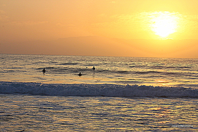 Surfers in Playa de las Americas, in the background the island of La Gomera