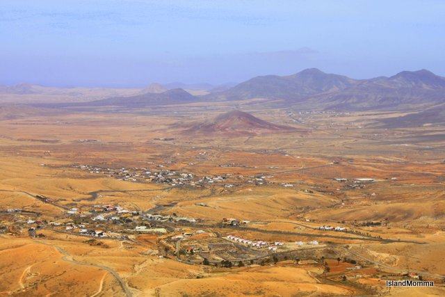 Volanic mounds rise, brown and purple from the earthy plain. Fuerteventura, Canary Islands