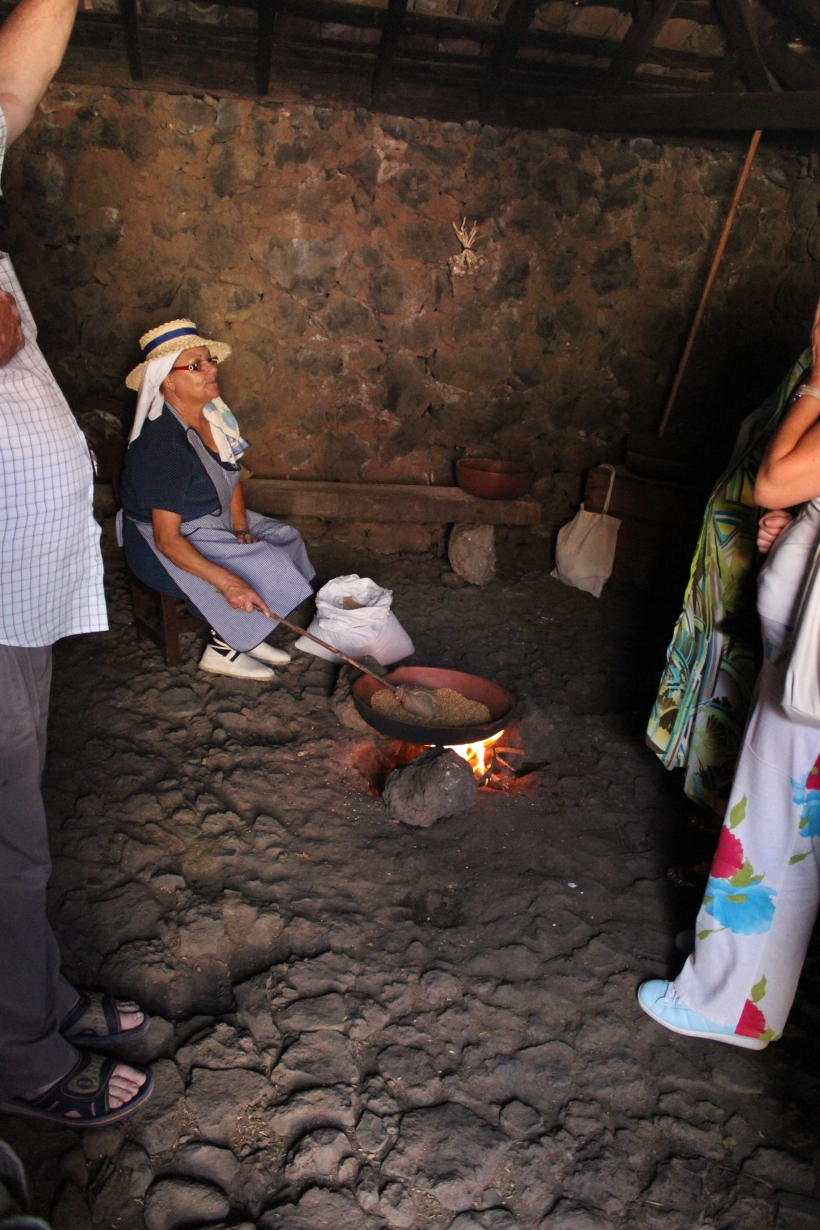 At El Dia de las Tradiciones in Chirche in Guia de Isora in Tenerife, a woman demonstates how grains and seeds were toasted at home before milling.